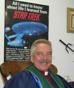 Author Photograph; Andrew Jensen in front of a Star Trek poster.
